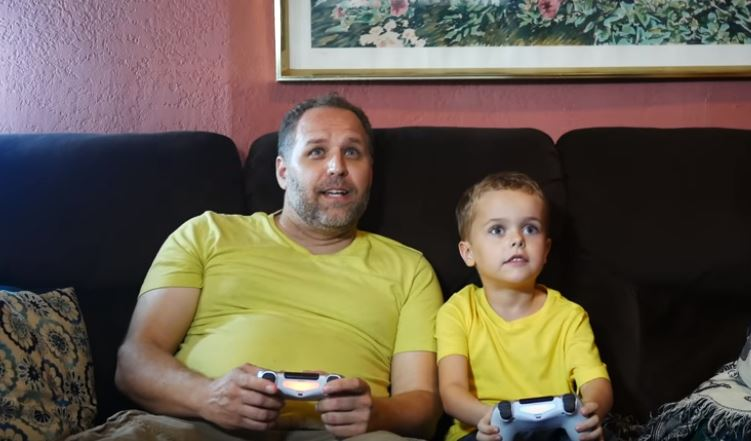 Father and son bonding while playing video games in matching yellow shirts